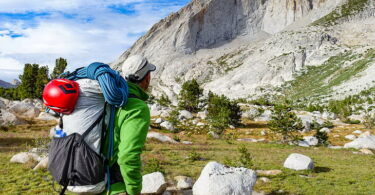 A man with an ultralight backpack gear looking at the mountains