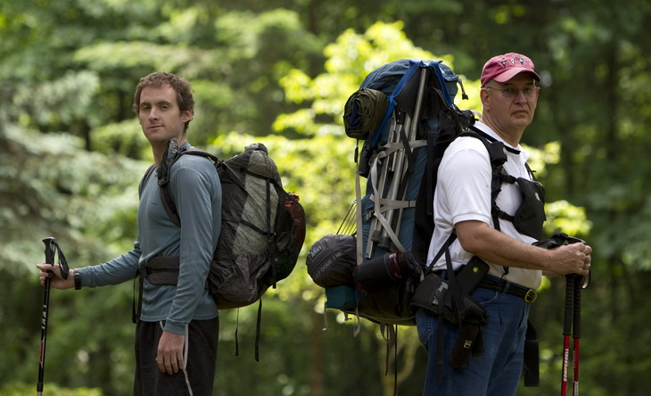 Two men with backpacks looking at the camera on a forest road