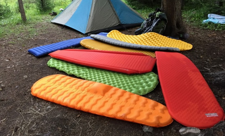 Ultralight sleeping pads on the ground near a tent in the forest