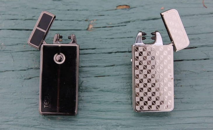 Two arc lighters on a wooden table