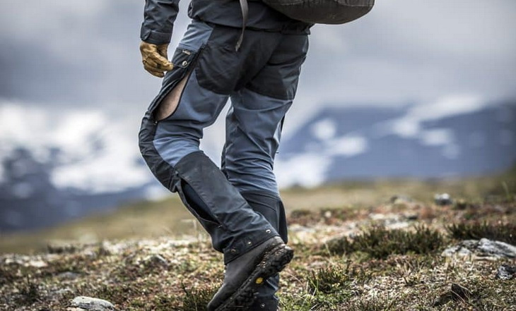 Man wearing a pair of rain hiking pants climbing the mountains