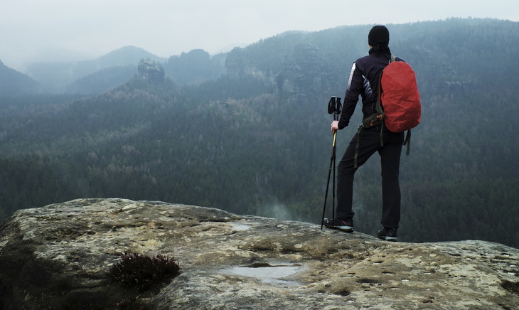 Hiker with red backpack on sharp sandstone rock in rock empires park and watching over the misty and foggy spring valley to Horizon.