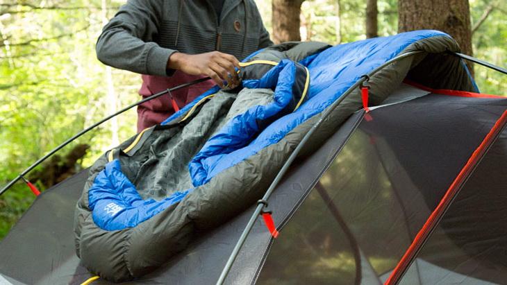 A man fixing a sleeping bag on a tent