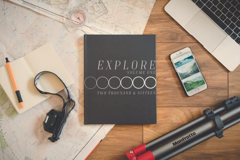 Explore Book Beside Silver Iphone 6 on Brown Wooden Surface