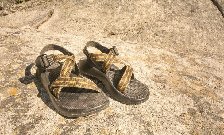 a pair of sport hiking sandals sitting on the ground in the sun