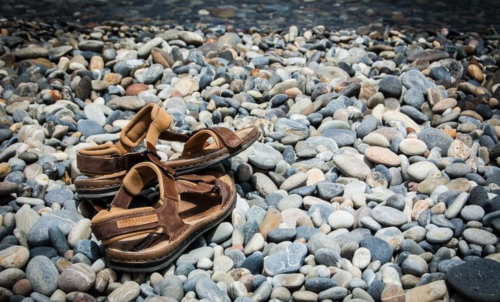 A pair of sandals of rocks near a water