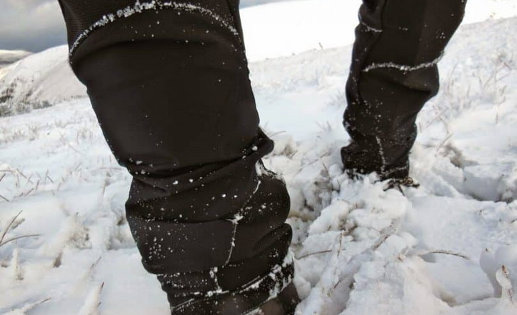 Image of a mans legs in the snow wearing a softshell hiking pants