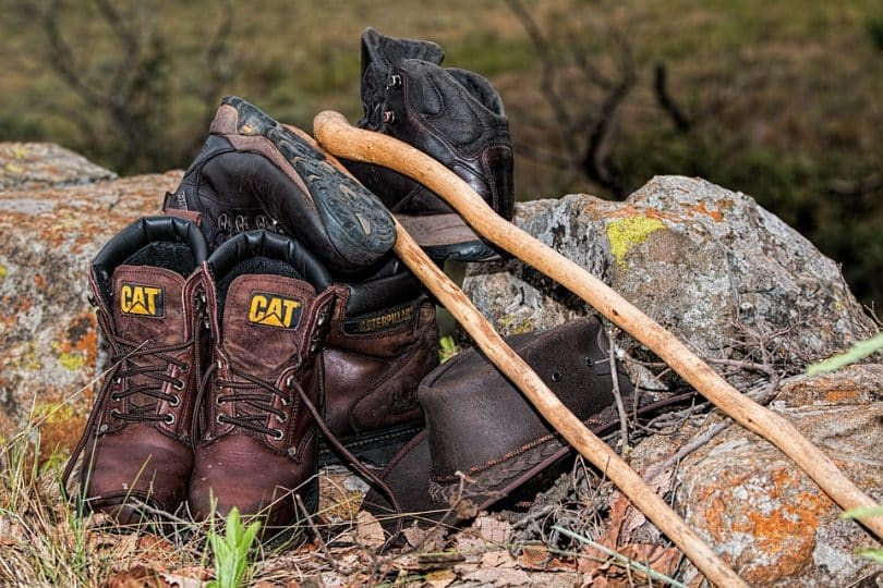 a picture of two hiking pairs of shoes and a hat