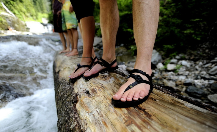 Image of a man legs wearing a pair of sport sandals while hiking