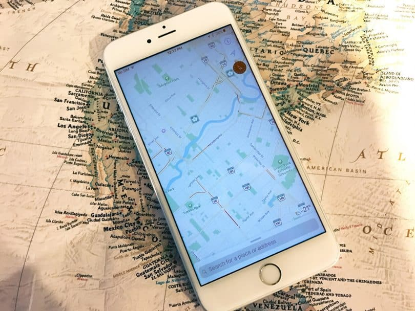 an iphone sitting on a map