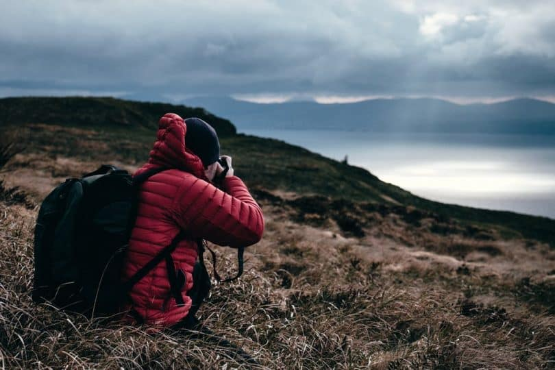 Person in Red Hoodie Taking a Photo of Wilderness