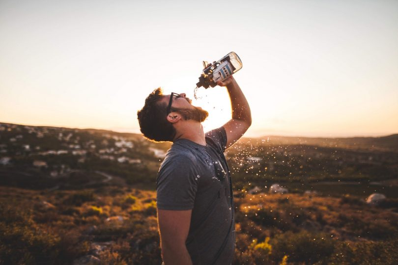 Man Pouring Water Bottle on His Mouth