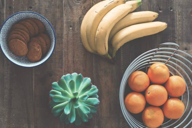 a picture of a yellow bananas beside oranges