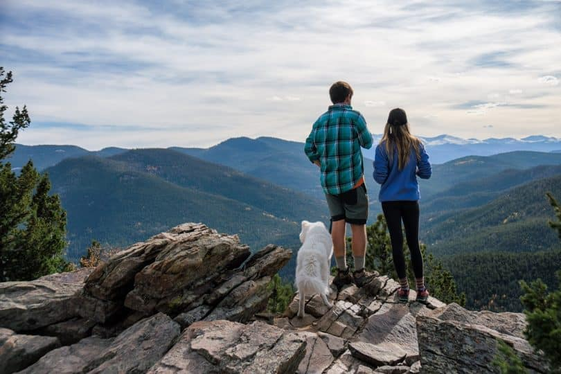 a man and his wife backpacking with their dog