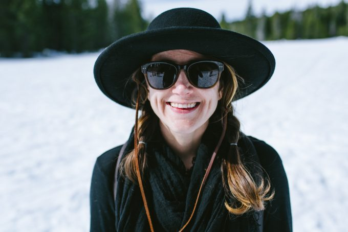 smiling-woman-with-hat-and-sunglasses-on-the-snow