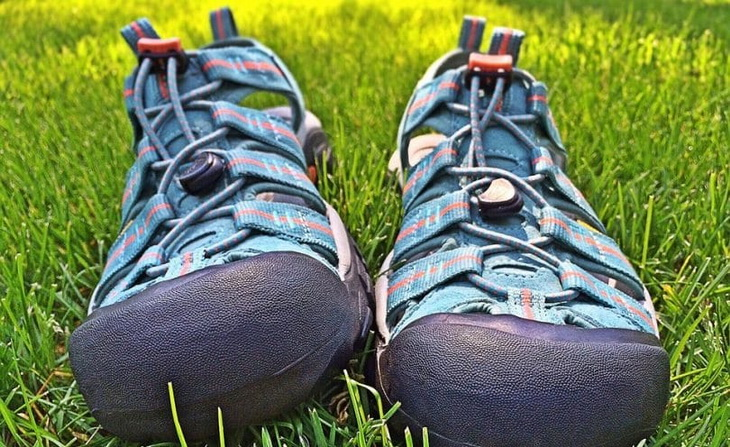 A pair of sport sandals for hiking on the grass