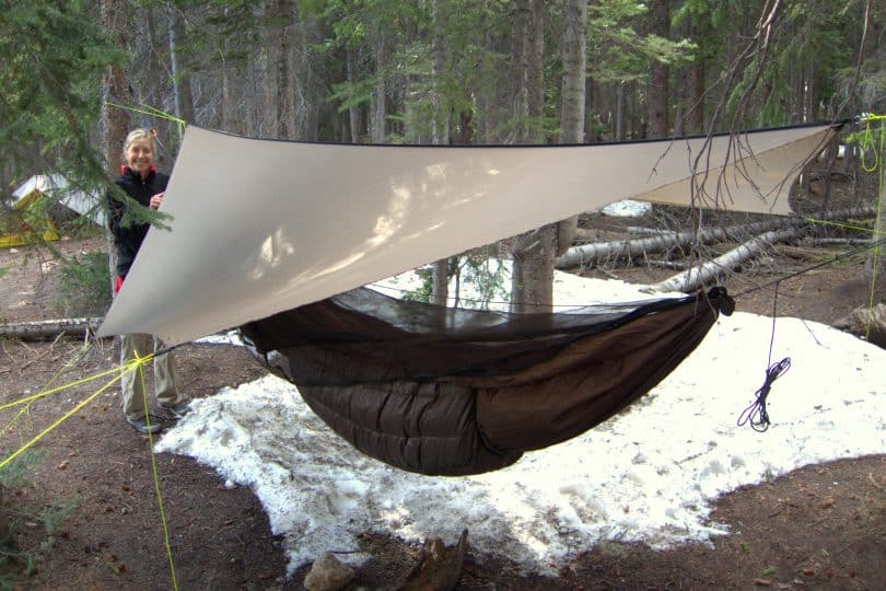 woman sitting next to a hammock shelter