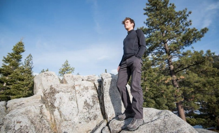 A men wearing a base layer sitting on a rock and looking at the landscape