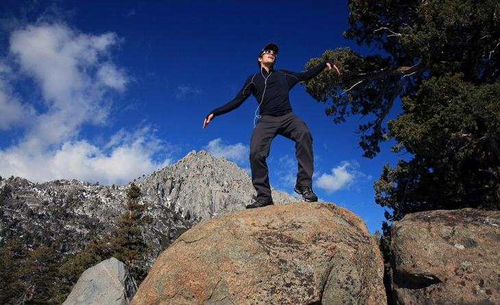 A man wearing a base layer dancing on a rock on top of the moutains