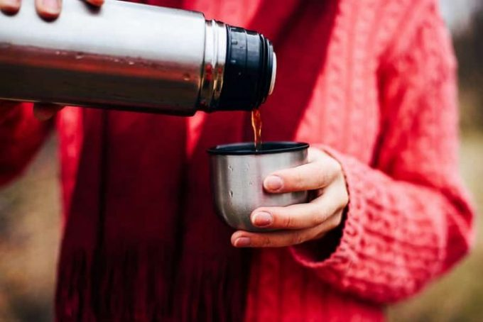 A person pouring coffee from a thermos