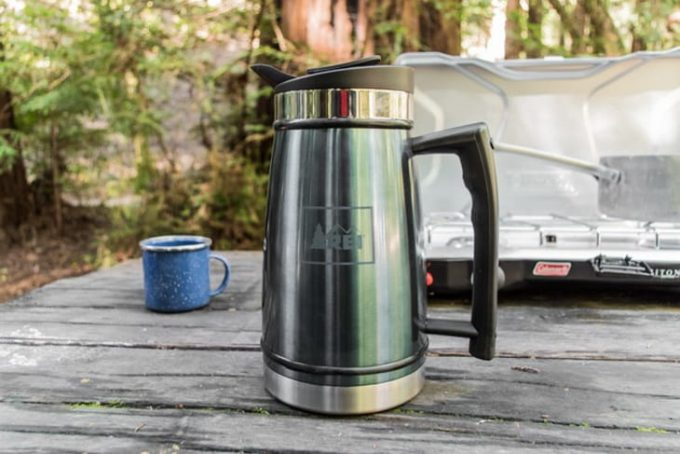 Image showing a camping thermos on a wooden table in the garden