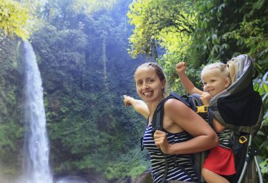 Mother hold baby girl in backpack on waterfall background