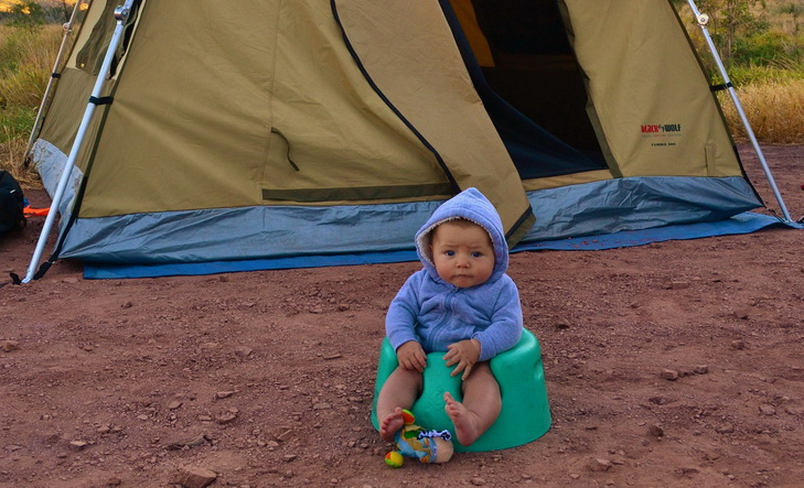 Little baby sitting on a seat in front of a tent
