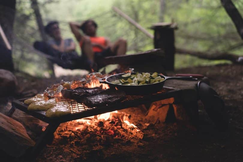 Black Non Stick Pan on Black Metal Charcoal Griller With Steak on Outdoor Forest With Two Persons Seating on Hammock