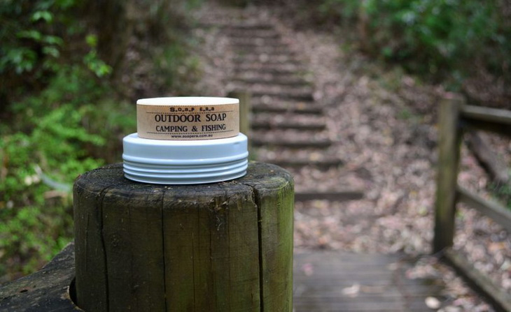 A camping soap sitting on a wood and some stairs on the background