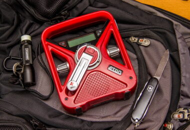 Image of Eton FRX3 Smartphone Charger and Radio, a Flashlight and a Knife on a backpack