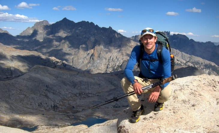 Image of a backpacker on top of the mountain