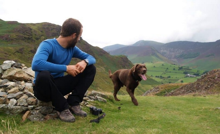 A man wearing a base layer is looking at his dog