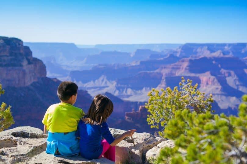 Toddlers Sitting on Rock during Daytime