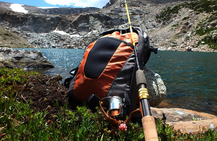 A fishing rod sitting on a backpack and a lake landscape
