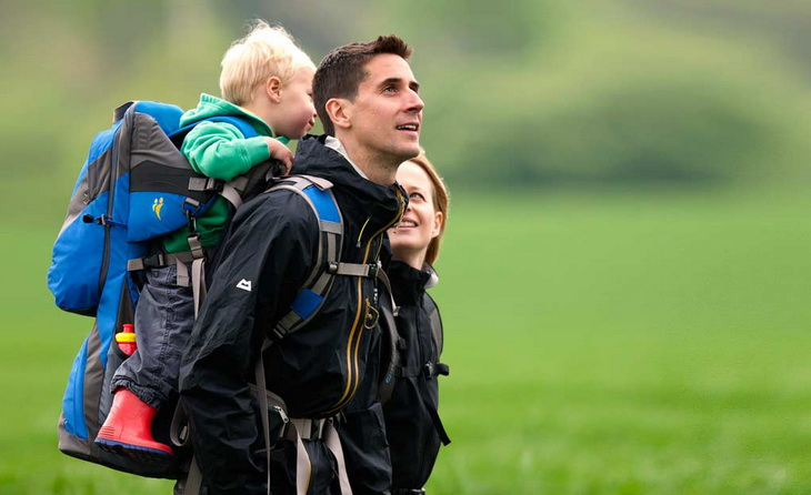 A toddler carried by his father in a backpack