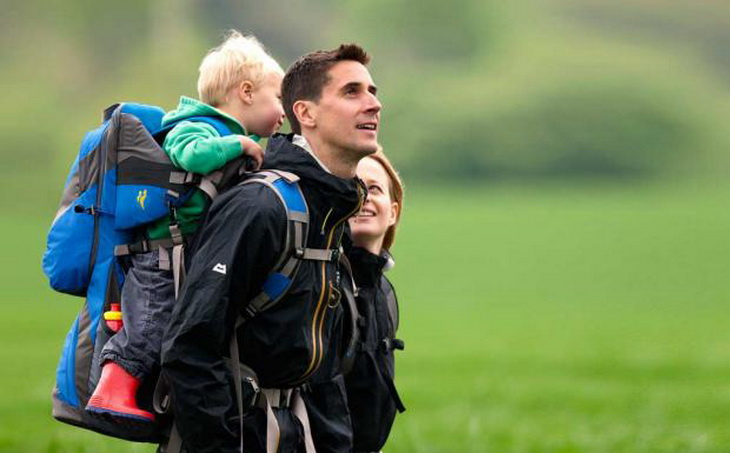 two adults hiking with their baby