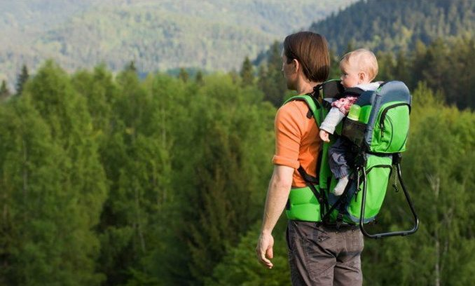 father carrying his little child in the nature
