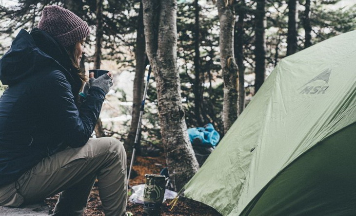 Woman hiker enjoying a cup of coffee and peace around her