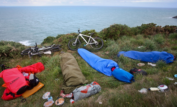 Bivy sacks and a couple of bikes and an ocean landscape