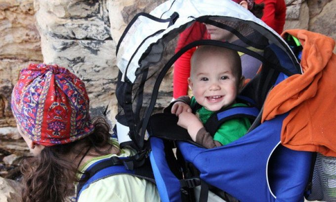 picture of a child in a baby carrier smiling at the camera