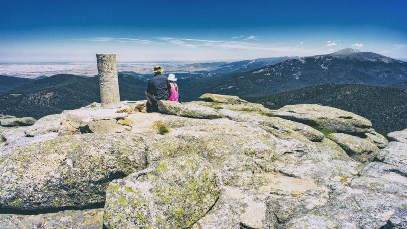 Man and Woman Sitting on RMountain during Daytime