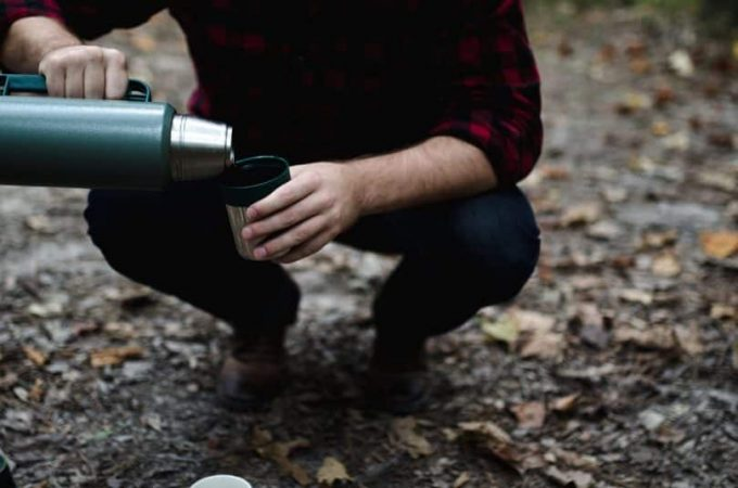A man pouring some coffee in a cup of a camping thermos