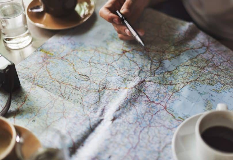 a picture of a person holding a pen over a map