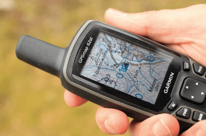 picture of a man holding a hiking GPS