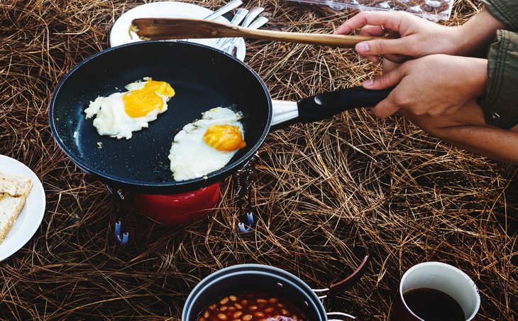 A man cooking eggs on a backpacking frying pan