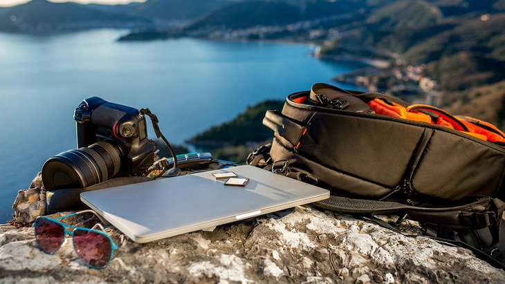 picture of a camera, a camera pack, a laptop and a pair of sunglases