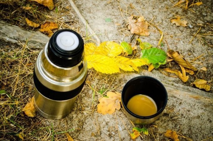 A camping thermos and a cup of coffee on the ground