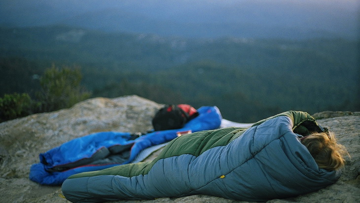 photo of a woman in a sleeping bag on the top of the mountains