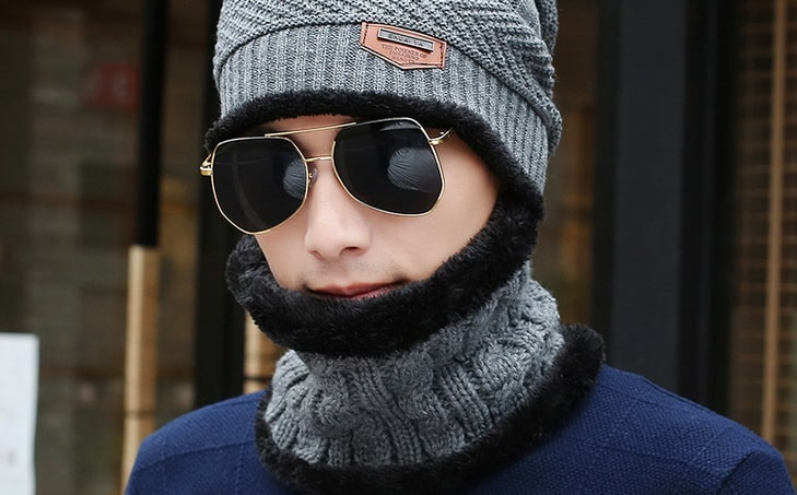 Woman posing with a neck gaiter and a pair of sunglasses