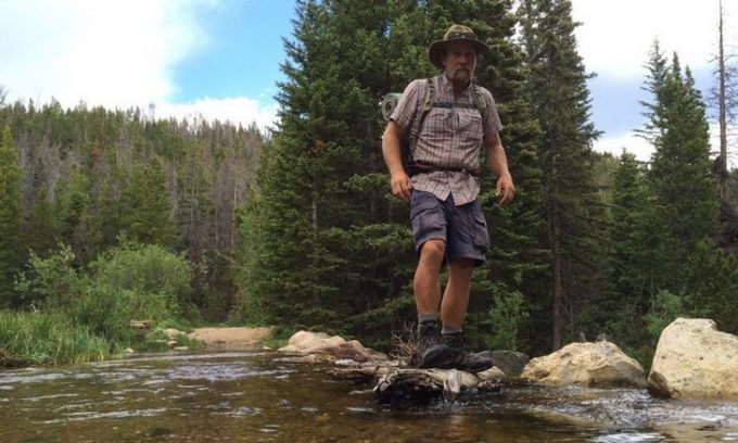 man with backpack crossing stream